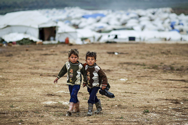 Syrian boys, whose family fled their home in Idlib, walk to their tent, at a camp for displaced Syrians, in the village of Atmeh, Syria, Monday, Dec. 10, 2012 Photo by Freedom House